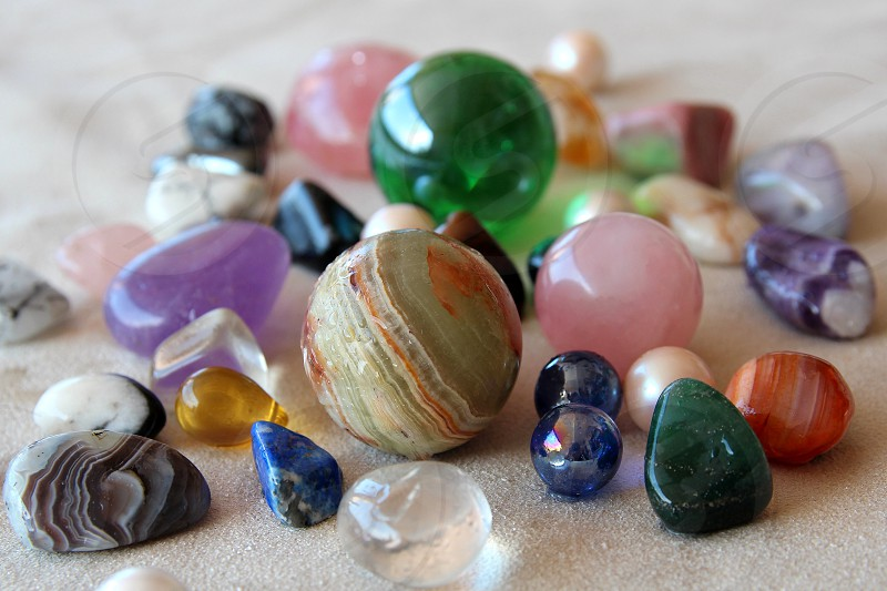 green pink and blue marbles on sand photo