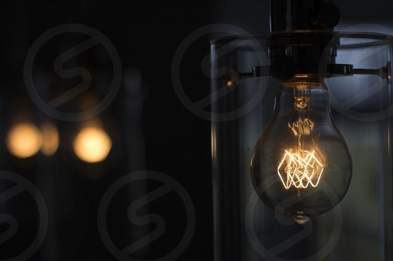 turned on bulb on metal pipe photo