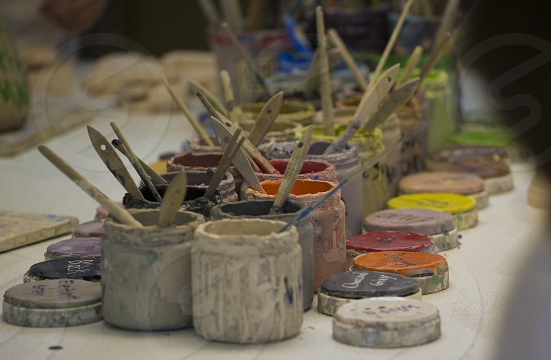 Set of different colored paints with brushes in each paint jar photo