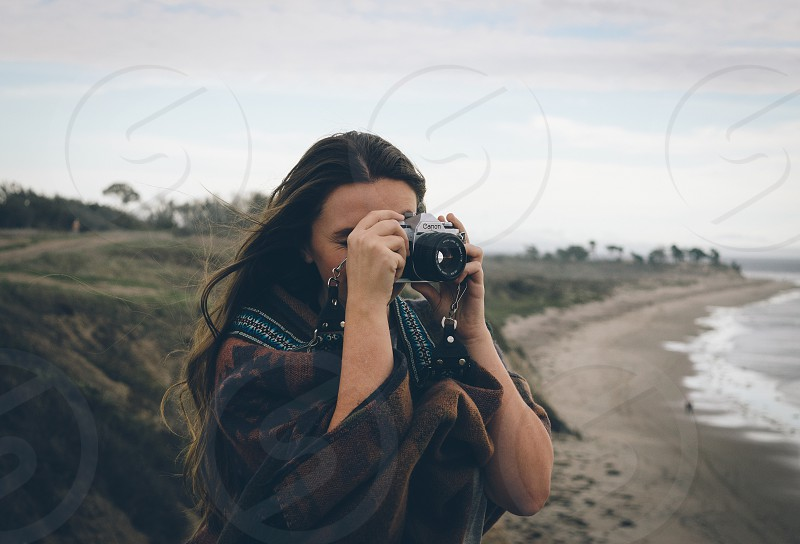 brown haired woman wearing brown black and white poncho holding silver and black dslr camera near beach under cloudy skies during daytime photo