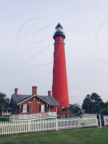 red and black lighthouse with white fence photo