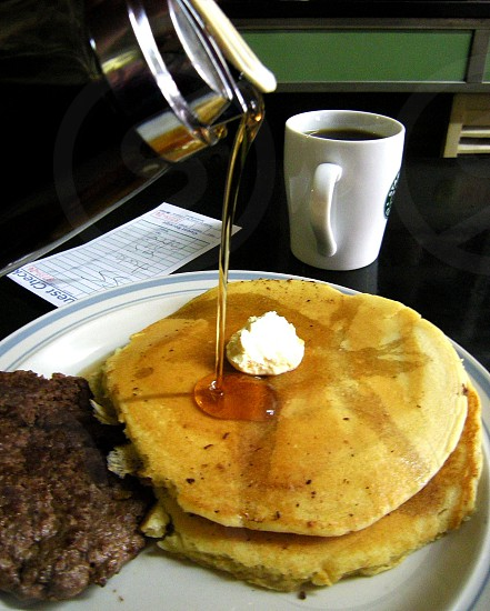 Syrup pour on pancakes with butter coffee hamburger steak and guest check photo