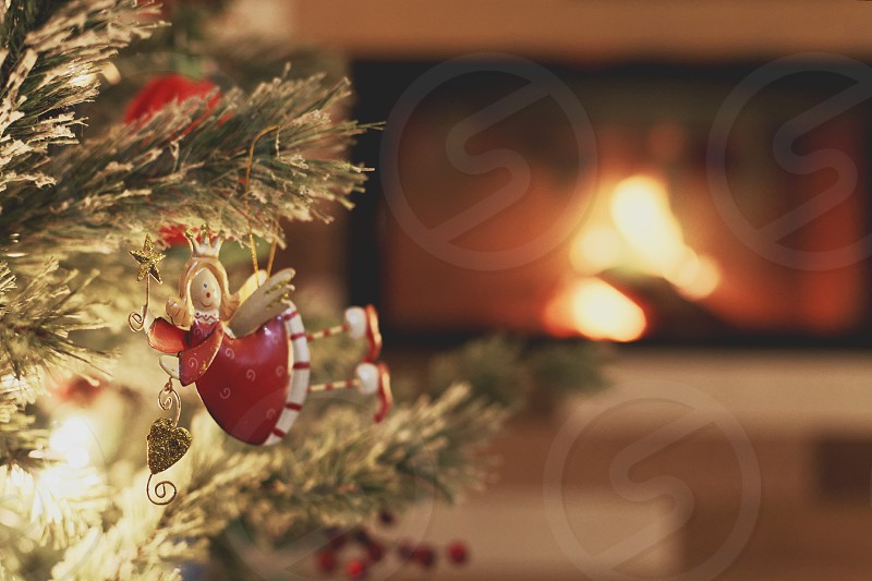red angel ornament on a tree with fireplace in the background photo