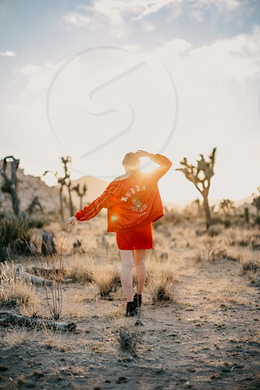Woman walking towards sunset in the desert photo