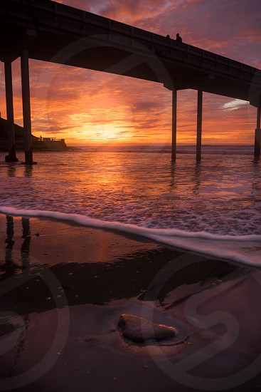 I beautiful fiery sunset underneath the Ocean Beach San Diego Pier - the second longest concrete pier on the West Coast. photo