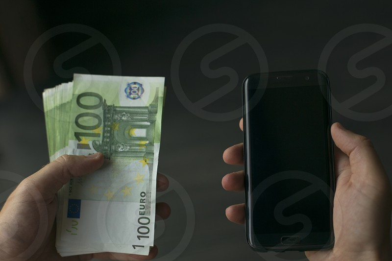 close up of hands holding one hundred euro bank notes and mobile phone photo