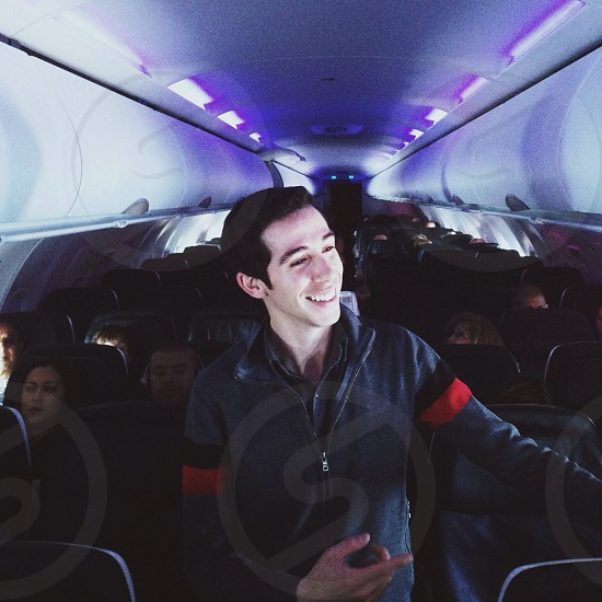 man in grey sweater walking down the center aisle of an airplane photo
