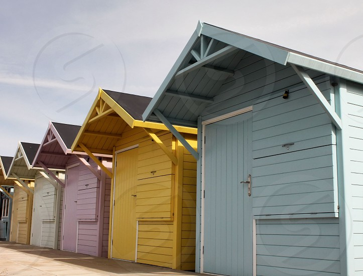 Colorful beach huts blueyellowpinkcreamorangeon the beach photo