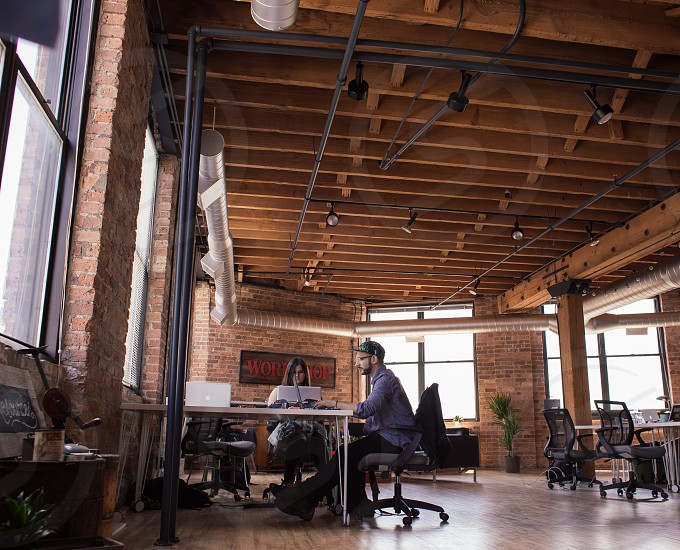 man and woman sitting at desk in brick loft office space photo