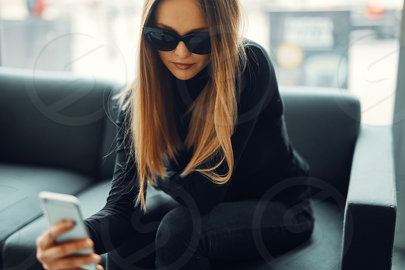 Young pretty girl sit on the sofa wear glasses and smile to camera photo