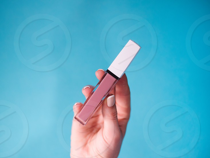 beautiful beige lip gloss in female hand isolated on blue background. photo