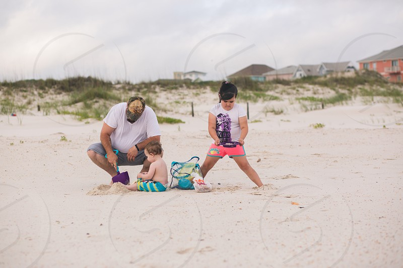 Family vacation beach sand play summer father son daughter photo