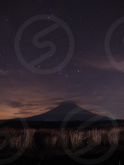silhouette of mountain under white clouds near green grass under black sky with stars during night time photo