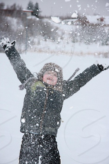 child wearing black winter jacket playing on snow photo