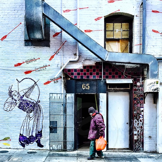 Woman walking past a mural.  photo