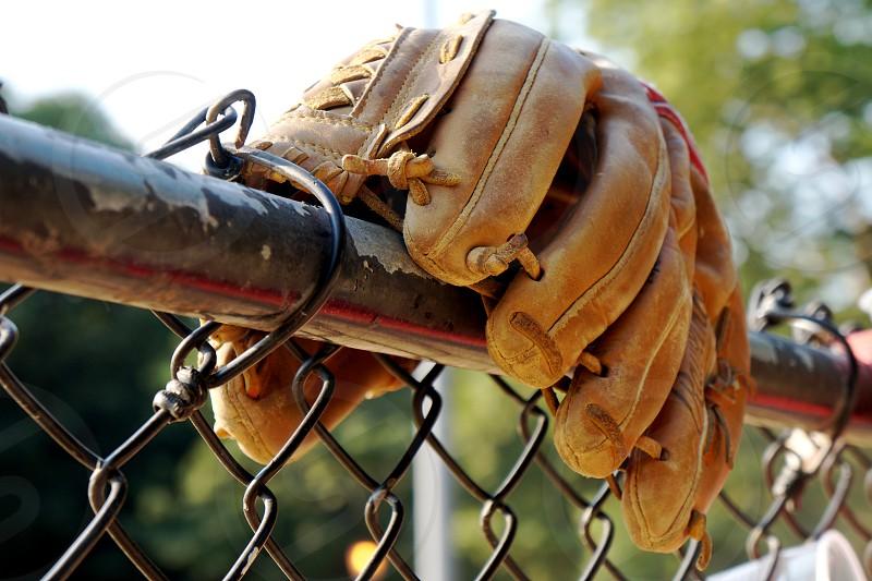 brown baseball glove on metal fence macro shot photo
