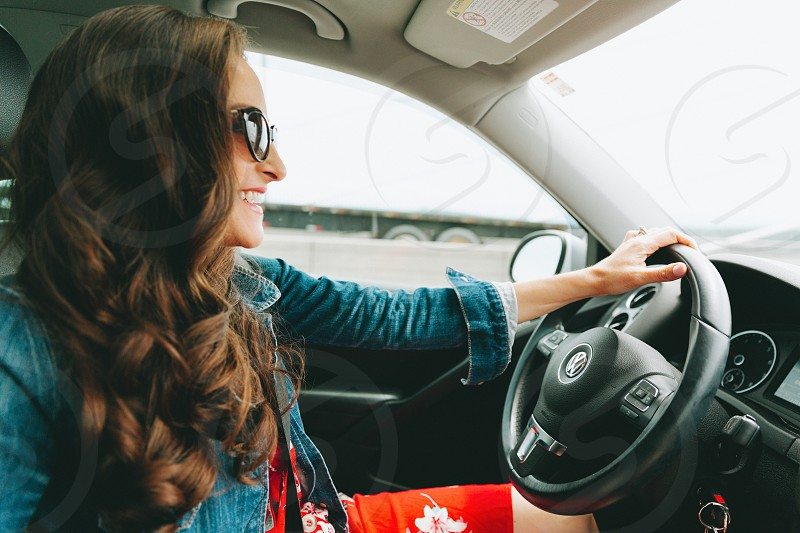 A beautiful woman driving a car and smiling. photo