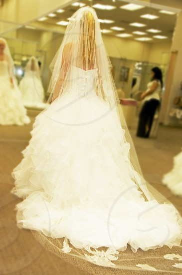 young lady looking in mirror while trying on wedding dress photo