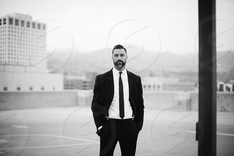 grayscale photography of man in formal suit standing near pole photo