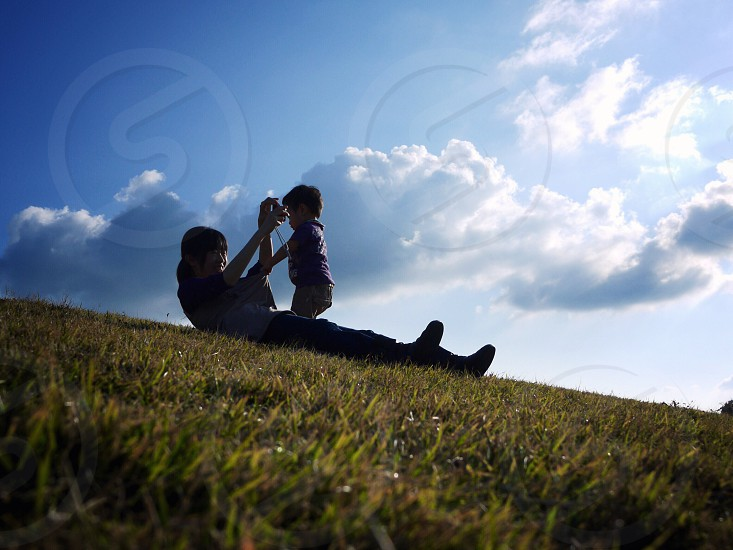 woman lying down on green grass playing with baby photo