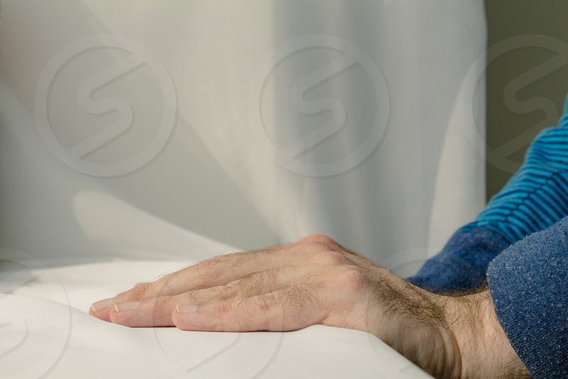 Man leaning and puts his hands down on white cloth background. photo