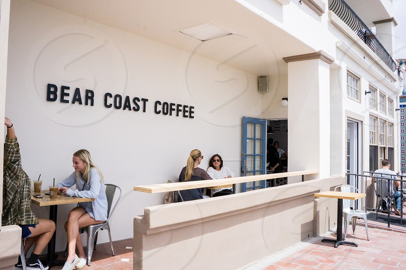 people sitting on chair on bear coast coffee shop on white concrete building during daytime photo