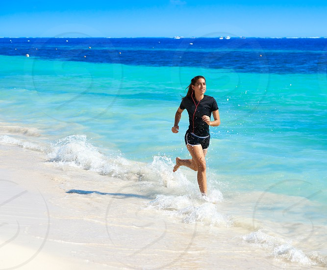 Latin girl running in caribbean shore beach of Mayan Riviera of Mexico photo