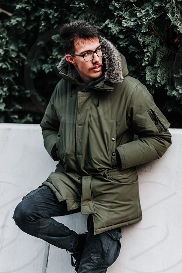 Young man in winter jacket posing outdoors photo