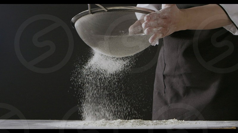 Professional chief sieves flour with sifter on a dark wooden table on a black background. Slow motion Full HD video 240fps 1080p. Step by step dough preparation. photo
