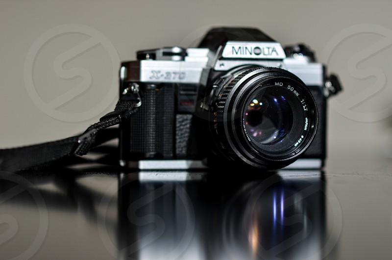 black and silver Minolta DSLR camera on table photo