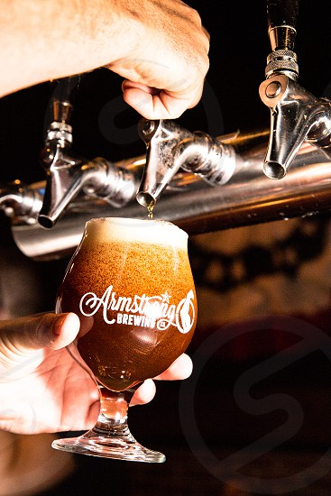 person filling armstrong brewing print in clear wine glass photo