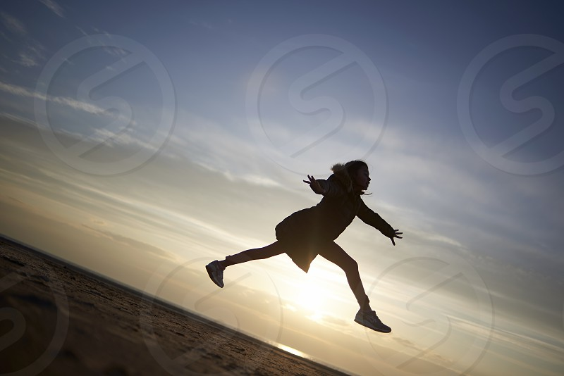 Silhouette of a young girl jumping high into the air like a dancer at the beach during sunset photo