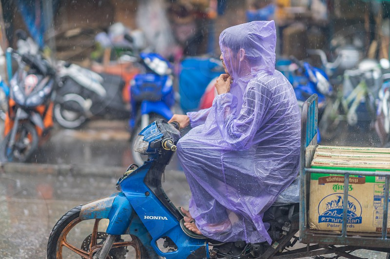 A man rides a motorcycle in the rain. Taken in Thailand. photo