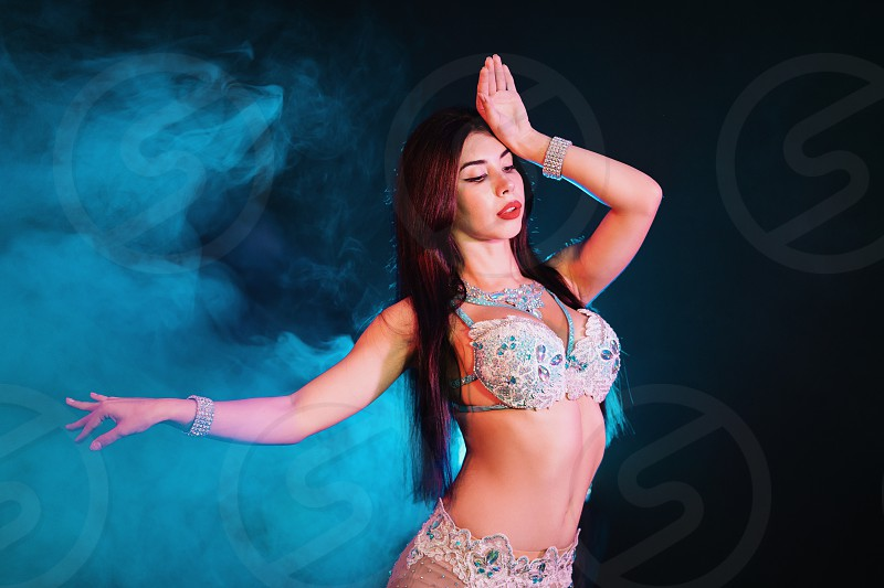 adorable sexy traditional oriental belly dancer girl dancing on luminous smoke background. Woman in white exotic costume sexually moves her semi-nude body. photo
