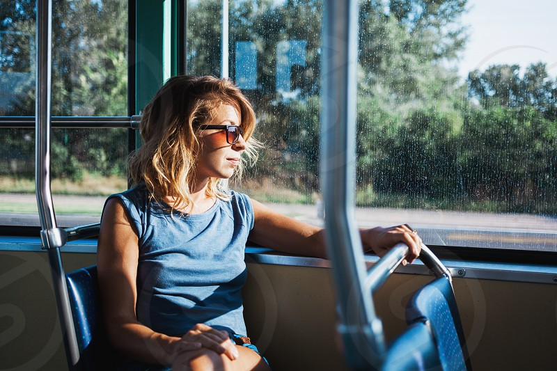 Young woman riding a public bus on a sunny day photo