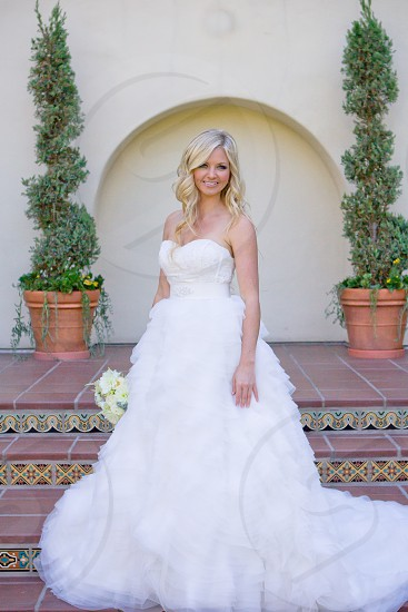 blonde woman in white tube lace wedding dress smiling while holding a white and light green flower bouquet against 3 step stairs and green plant in brown round pot in the background photo