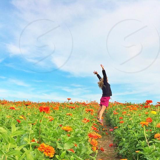woman jumping near orange flower field photo