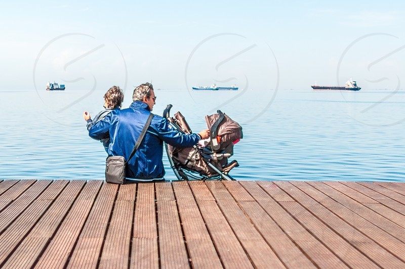 man sitting on boat dock while holding two child near body of water during daytime photo