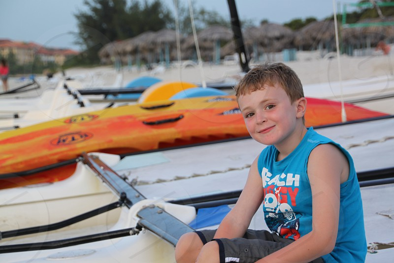 young child boy on a beach with sailbaots in backdrop photo
