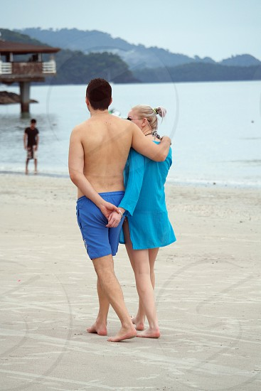 man wearing blue shorts besides woman in blue jacket while holding her hands near man in black t shirt besides sea water during daytime photo