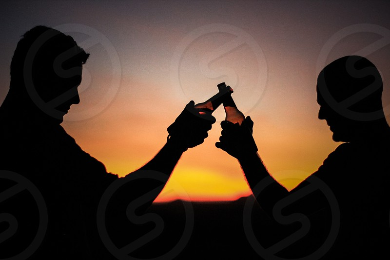 Two people clinking cheers silhouette  photo