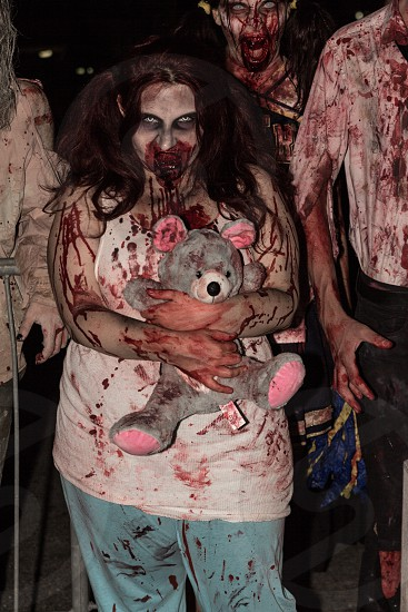girl with maroon hair in white tank top holding bear zombie costume photo