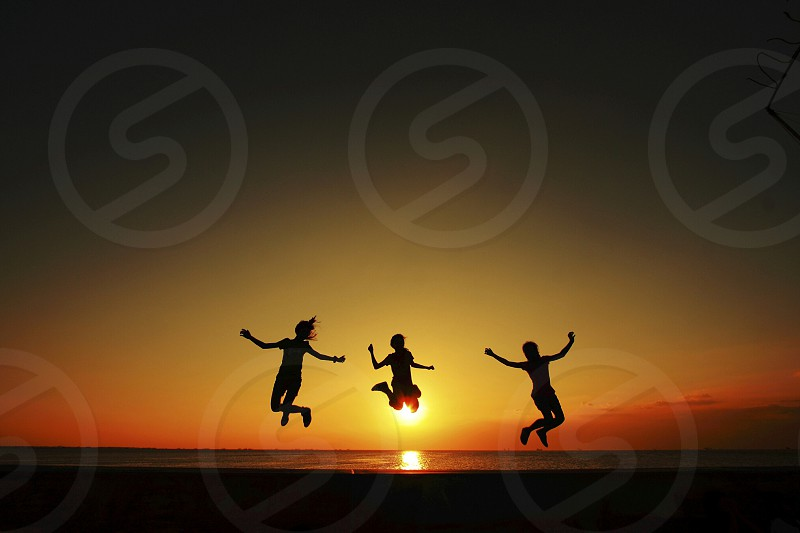 silhouette photo of three people gaining the momentum of doing a jump shot during sunset photo