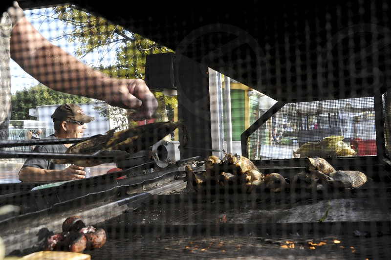 Grilling corn on big outside grill with tongs photo