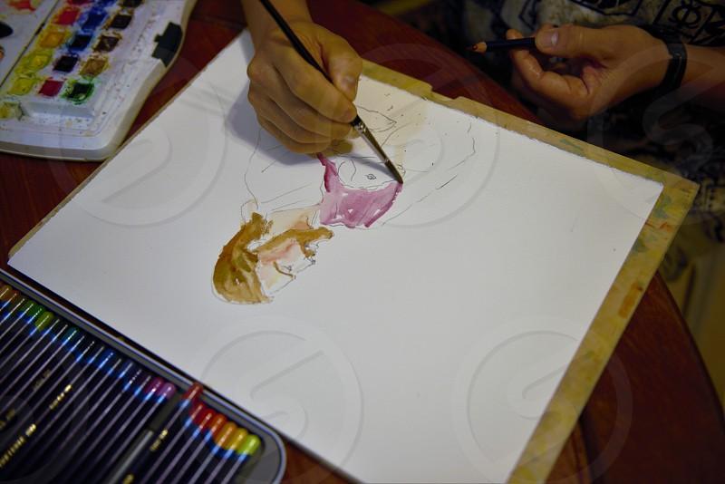Man painting image using watercolors in Hong Kong.   photo