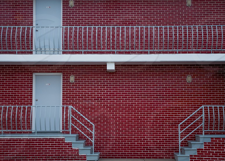 gray metal handrails and gray door with red bricked wall photo