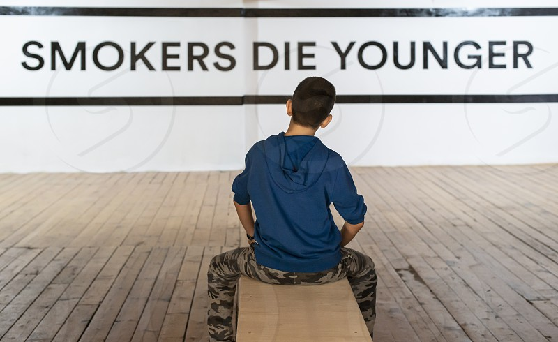 Teenager smoking and message on wall - Smokers die younger. No smoking concept with child. Casual clothes. photo