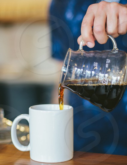 Hand Pouring Glass Cup into White Ceramic Mug photo
