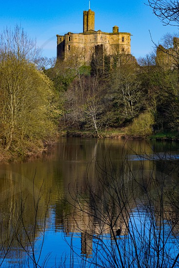 Warkworth castle reflection on the Croquet river Northumberland England  photo