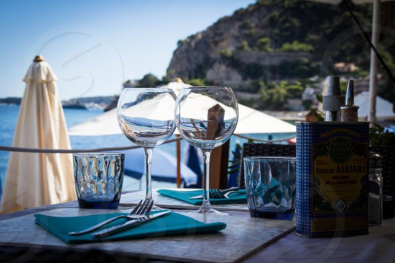 beachside restaurant cafe wine glasses dining table ocean umbrella romantic vacation photo
